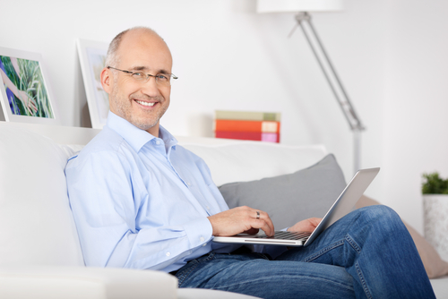 man sitting on couch with laptop in lap